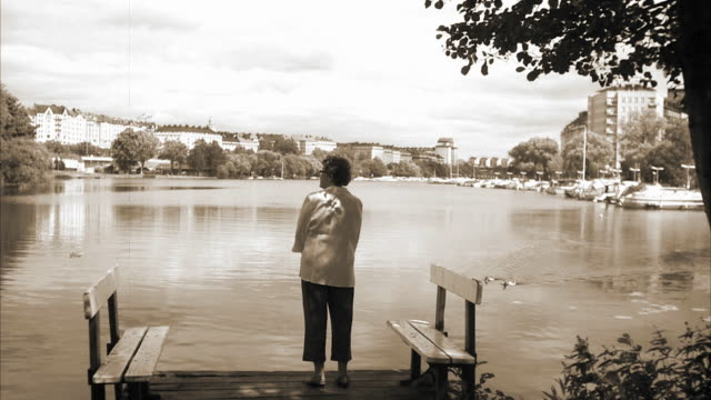 stockvideo's en b-roll-footage met an elderly woman standing on a jetty stockholm sweden. - sepiakleurig
