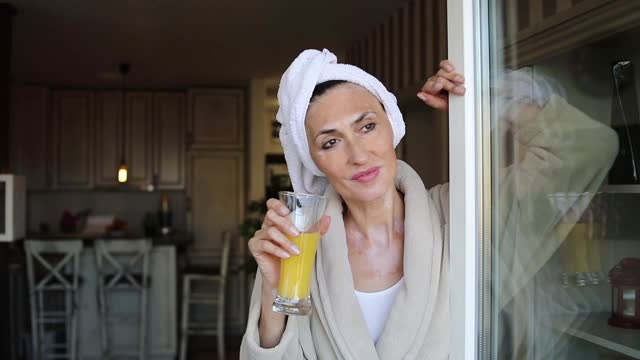 an elderly woman standing on the terrace at home drinking orange juice - woman drinking orange juice on the balcony - bathrobe stock videos & royalty-free footage
