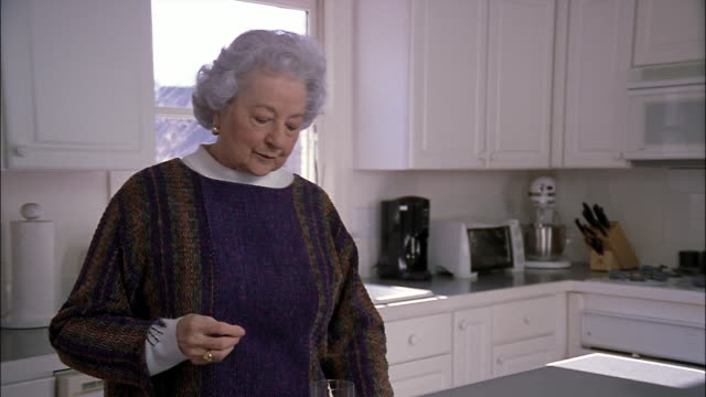 an elderly woman swallows a prescription pill with a glass of water. - taking medicine stock videos and b-roll footage