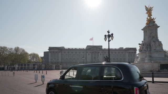 an electric black cab taxi passes buckingham palace london in glorious afternoon spring sunshine - palace stock videos & royalty-free footage