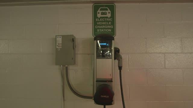 vídeos de stock, filmes e b-roll de an electric car charging station in an indoor parking garage in new york city new york on march 17th 2015 shots interior close shots of a woman... - carregamento eletricidade