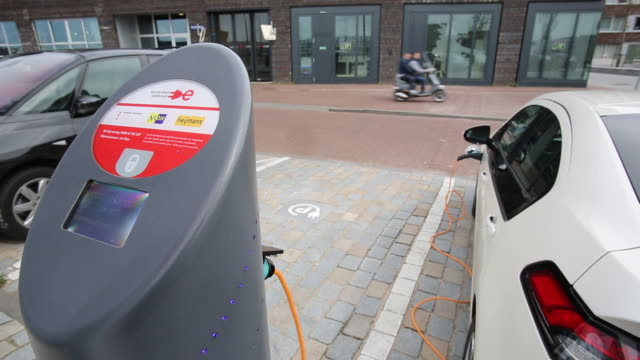 an electric car plugged into a recharging station in ijburg, amsterdam, netherlands. - tanken stock-videos und b-roll-filmmaterial
