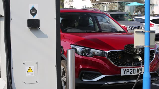 an electric car recharging in a car park in ambleside, lake district, uk. - electric vehicle stock videos & royalty-free footage