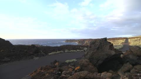 vídeos y material grabado en eventos de stock de an electric car travels along a coastal road on the island of el hierro. - coche eléctrico coche alternativo