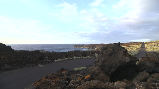 vídeos de stock, filmes e b-roll de an electric car travels along a coastal road on the island of el hierro. - hierro