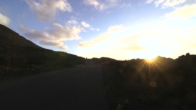 vídeos de stock, filmes e b-roll de an electric car travels along a road on the island of el hierro. - hierro