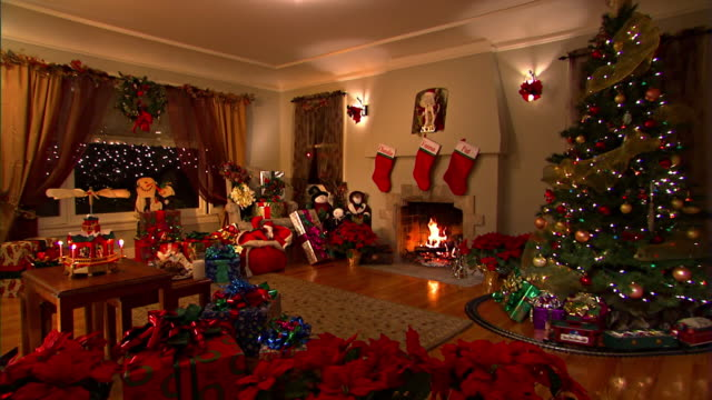 an electric train circles a tree in a living room decorated with symbols of the christmas holiday. - 暖炉点の映像素材/bロール