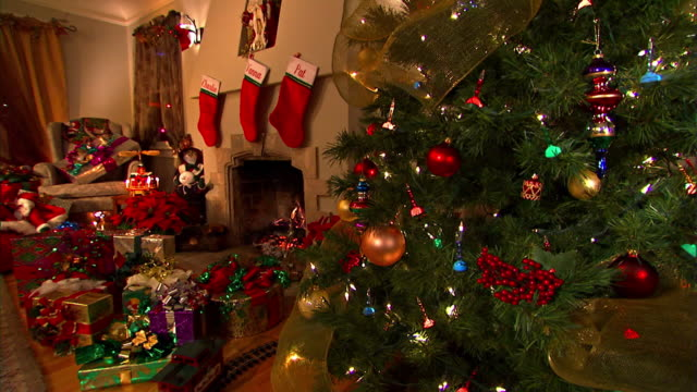 an electric train circles a tree in a living room decorated with symbols of the christmas holiday. - stockings stock videos & royalty-free footage