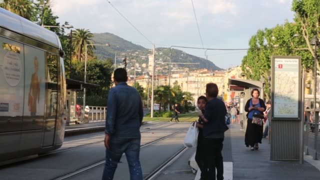 vidéos et rushes de an electric tram stands at a passenger stop as residential property sits beyond in nice, france, on thursday, may 14, 2015 - tram