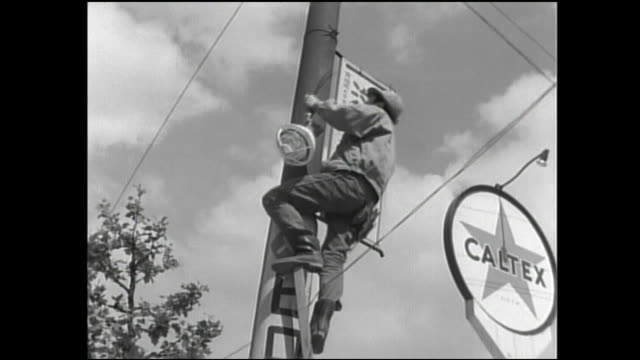 an electrician climbs a utility pole to install a streetlight. - maintenance engineer stock videos & royalty-free footage