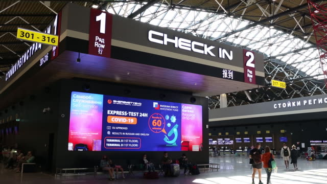 an electronic billboard displaying information about covid-19 express testing at terminal b at the sheremetyevo airport in moscow, russia, on monday,... - russia点の映像素材/bロール