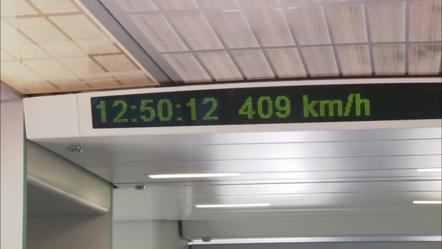 vídeos de stock, filmes e b-roll de an electronic sign shows the time and kilometers per hour in a high-speed rail train. - 2015