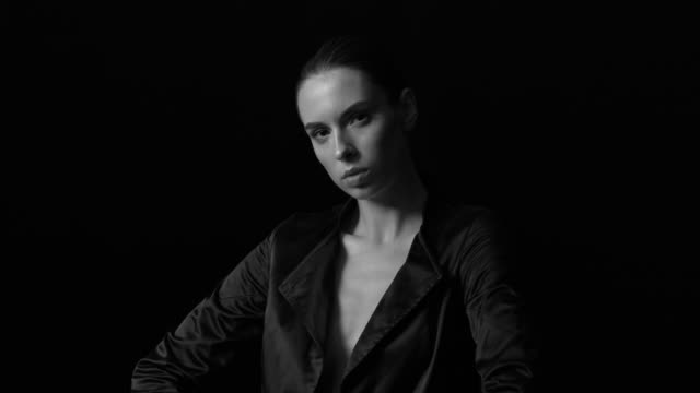 vídeos de stock e filmes b-roll de an elegant young woman in a black jacket looks defiantly at the camera. black and white video. - casaco curto com mangas