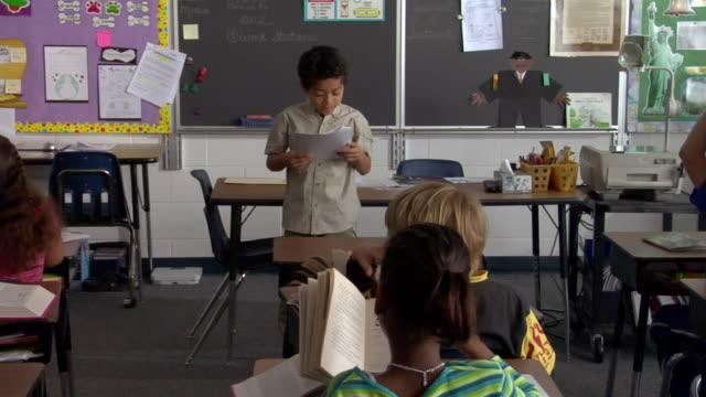 vídeos y material grabado en eventos de stock de an elementary school boy reads his report in front of the class. - ponencia discurso