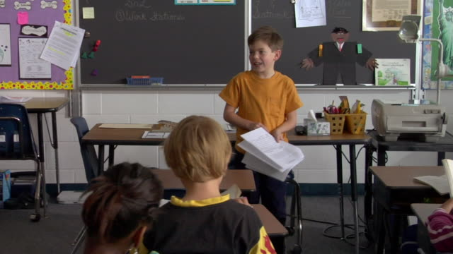 An elementary school boy reads his report in front of the class.