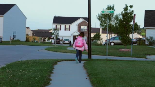 An elementary school girl runs around a sidewalk corner in Indianapolis, Indiana.