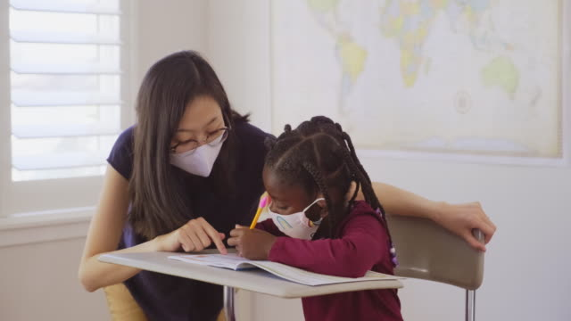 an elementary school student and teacher in a classroom - education stock videos & royalty-free footage
