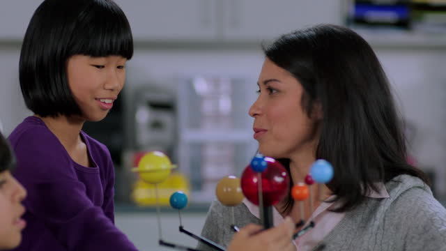 an elementary student discusses a model solar system with her teacher. - encouragement stock videos & royalty-free footage