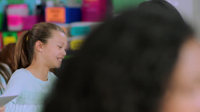 vidéos et rushes de an elementary teacher chats with one of her students about an assignment in class. - expliquer