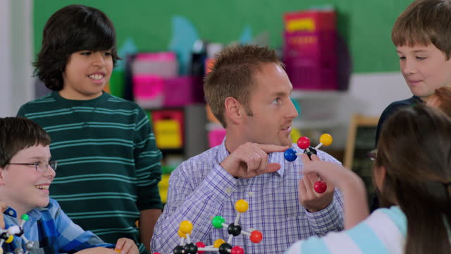an elementary teacher explains the components of a molecular model to his class. - goatee stock videos & royalty-free footage