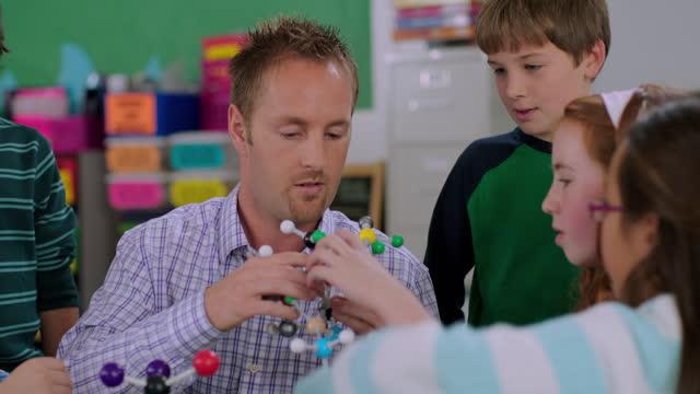 vídeos y material grabado en eventos de stock de an elementary teacher uses interactive learning to explain a molecular model. - biología