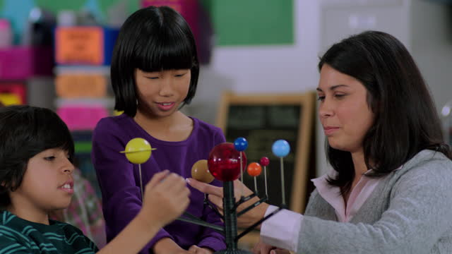 An elementary teacher works with two of her students on a model solar system.