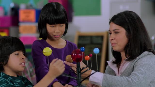 vídeos de stock e filmes b-roll de an elementary teacher works with two of her students on a model solar system. - sistema solar