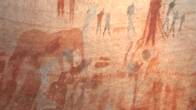 an elephant and bushmen are depicted in a petroglyph on a rock wall. available in hd. - prehistoric art stock videos & royalty-free footage