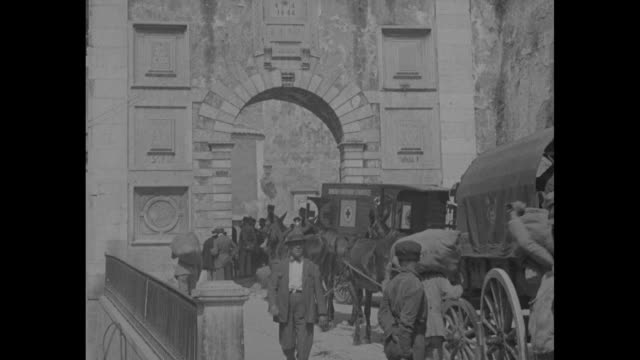 an elevated pan of lisbon / vs soldiers at an archway; two others seen through an archway; soldiers and horses at rest on a cobblestone street; men... - portugal stock-videos und b-roll-filmmaterial