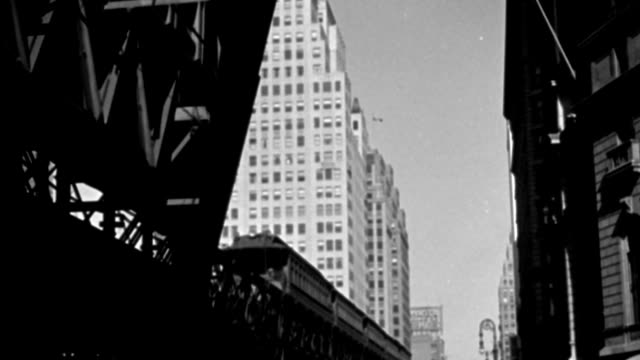 an elevated train drives on tracks over street traffic below. - 1944 stock videos & royalty-free footage