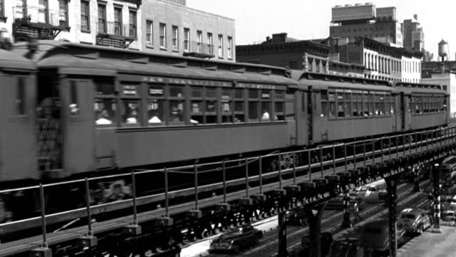an elevated train drives on tracks over street traffic below. - elevated train stock-videos und b-roll-filmmaterial