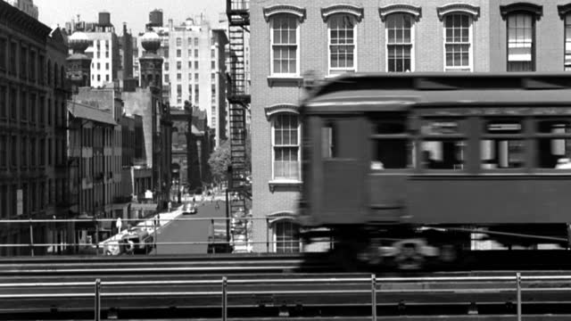 an elevated train drives on tracks past upper level windows of apartment buildings. - elevated train stock-videos und b-roll-filmmaterial