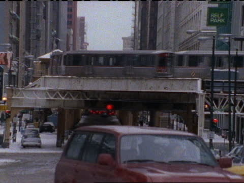 an elevated train drives through downtown chicago. - chicago 'l' stock videos & royalty-free footage