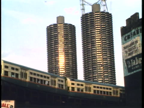 an elevated train moves over a trestle in front of the marina towers in chicago. - elevated train stock videos & royalty-free footage