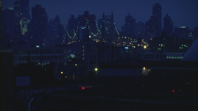 an elevated train moving on a railway track in manhattan at night. - クイーンズボロ橋点の映像素材/bロール