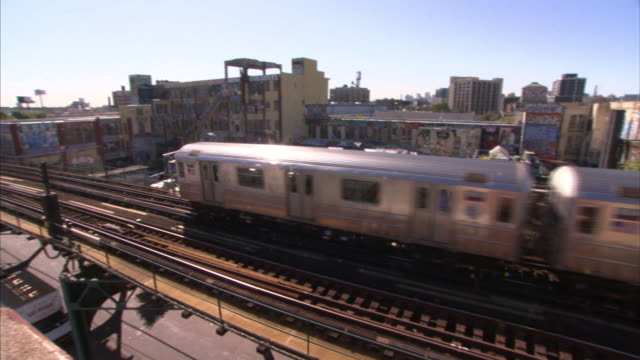 an elevated train passes above city traffic in queens. - elevated train stock videos & royalty-free footage