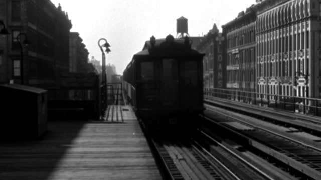an elevated train pulls alongside a train station platform and stops. - elevated train stock-videos und b-roll-filmmaterial