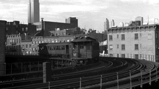 an elevated train pulls around a curve past city buildings. - 1940 stock videos & royalty-free footage