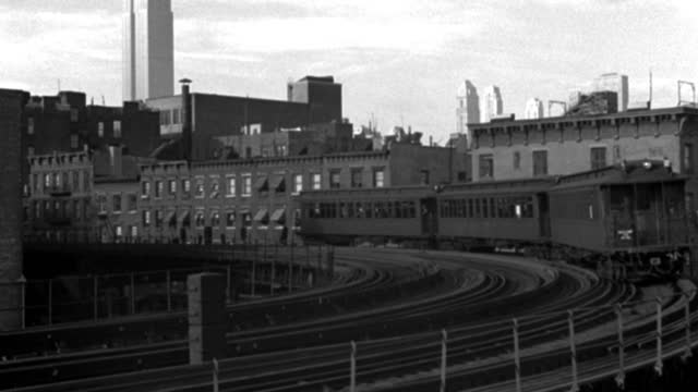 an elevated train pulls around a curve past city buildings. - elevated train stock videos & royalty-free footage