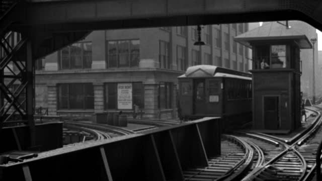 an elevated train pulls into a train station as another train leaves a few moments later. - 1935 stock videos & royalty-free footage