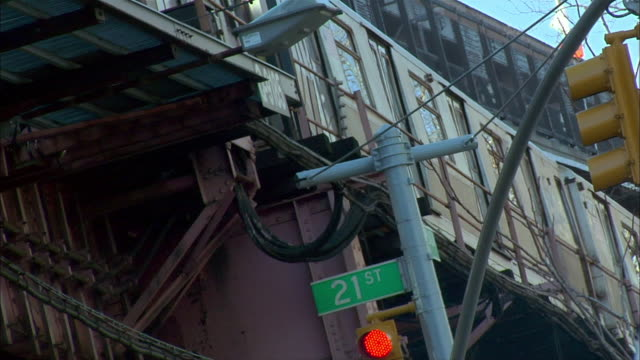 an elevated train runs above the 21st street sign in long island city, queens, new york city. - hochbahn passagierzug stock-videos und b-roll-filmmaterial