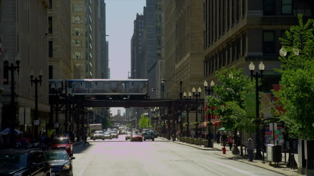 an elevated train speeds across a downtown street in chicago, illinois. - chicago 'l' stock videos and b-roll footage