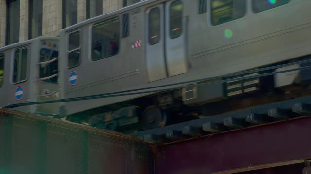 An elevated train speeds past an office building in Chicago, Illinois.