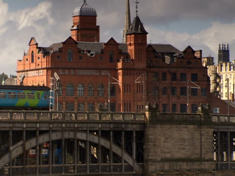 stockvideo's en b-roll-footage met an elevated train travels over a bridge. - zweeftrein