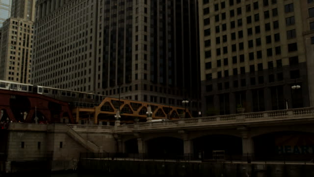an elevated trains travels between office buildings in chicago, illinois. - chicago elevated stock-videos und b-roll-filmmaterial