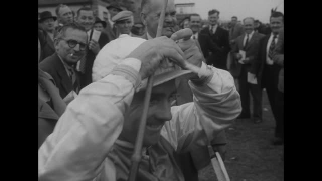 an elevated view of a crowd of thousands at the track's fence / a bookie with board 'taffy ltd' men notating slips of paper / a board with... - winnings stock videos and b-roll footage