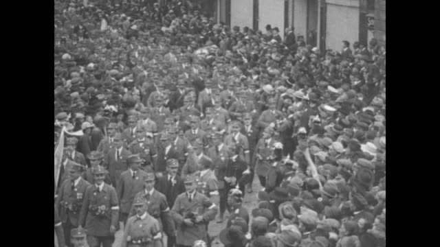 vs an elevated view of a parade of uniformed men marching through a crowd / adolf hitler wearing suit and tie looks on from open window / more of the... - passing a note stock videos & royalty-free footage