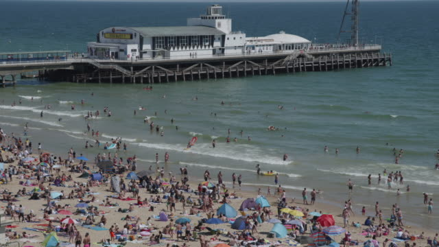 an elevated view of the large crowds that gathered on bournemouth beach in front of the pier, making social distancing very difficult on may 31, 2020... - pier stock videos & royalty-free footage