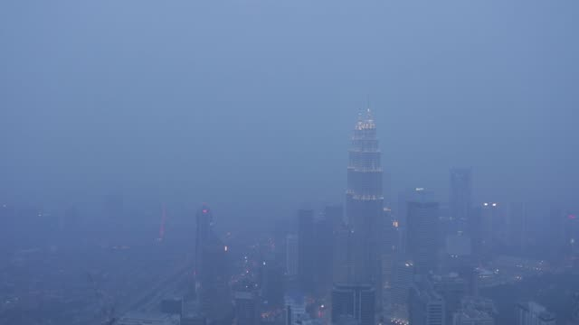 an elevated view shows the petronas twin towers and the rest of the city shrouded in haze at dusk in kuala lumpur malaysia on monday oct 19 lights... - petronas twin towers stock-videos und b-roll-filmmaterial