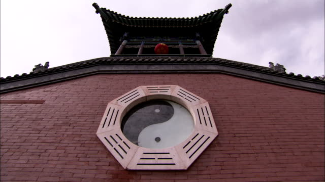 An emblem depicting the yin and yang symbols decorates China's Temple of the Ninth Heaven. Available in HD.